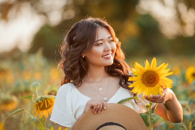 Jonge aziatische vrouw met krullend haar in een veld met zonnebloemen bij zonsondergang. portret van een jonge mooie aziatische vrouw in de zon. zomer.