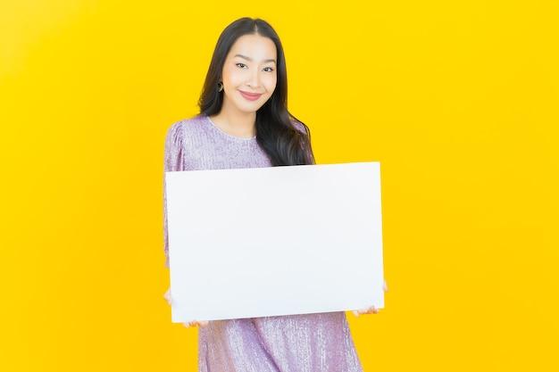 Jonge aziatische vrouw met leeg wit reclamebord op geel on