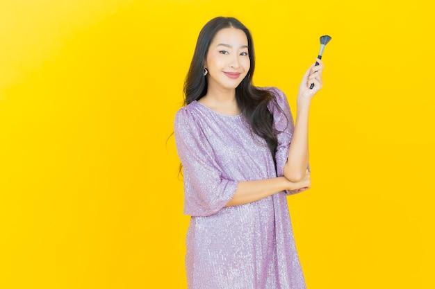 Jonge aziatische vrouw met make-up borstel cosmetica op geel