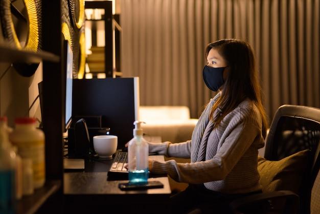Jonge aziatische vrouw met masker laat in de nacht werken vanuit huis