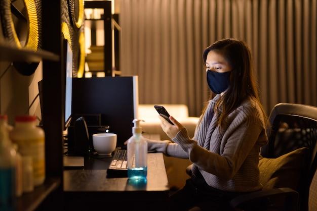 Jonge aziatische vrouw met masker met behulp van telefoon tijdens het werken vanuit huis 's nachts