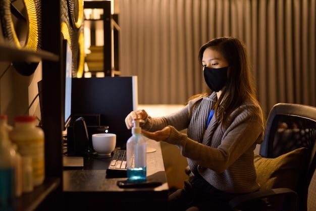 Jonge aziatische vrouw met masker met handdesinfecterend middel tijdens het werken vanuit huis 's nachts