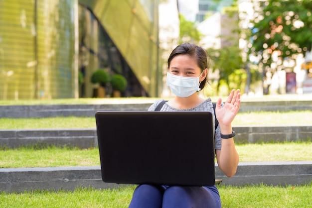 Jonge aziatische vrouw met masker videobellen met behulp van laptop zittend op de trap buiten
