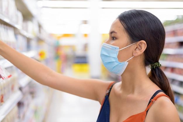 Jonge aziatische vrouw met masker voor bescherming tegen de uitbraak van het coronavirus die bij de supermarkt winkelen