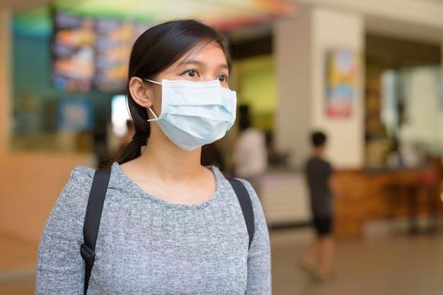 Jonge aziatische vrouw met masker voor bescherming tegen de uitbraak van het coronavirus in het restaurant