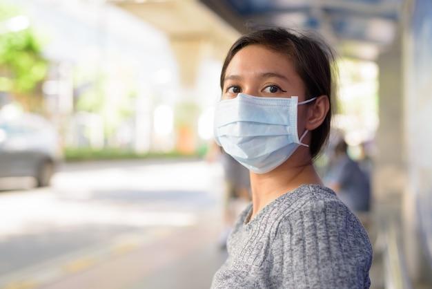 Jonge aziatische vrouw met masker voor bescherming tegen uitbraak van het coronavirus zit bij de bushalte