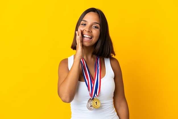 Jonge aziatische vrouw met medailles geïsoleerd op een witte achtergrond schreeuwen met wijd open mond