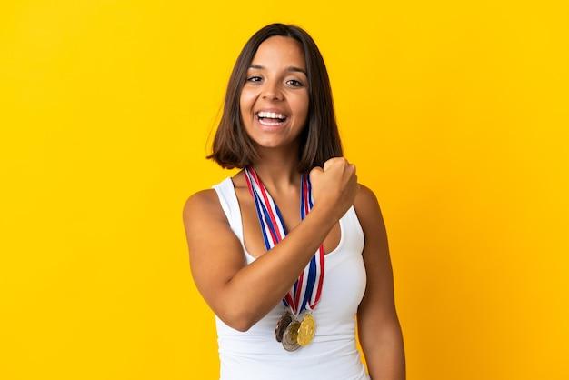 Jonge aziatische vrouw met medailles geïsoleerd op een witte muur een overwinning vieren