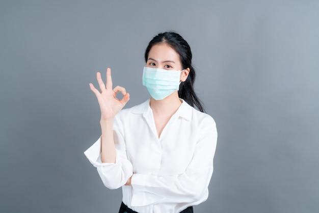 Jonge aziatische vrouw met medisch gezichtsmasker beschermt filterstof pm2.5 anti-vervuiling, anti-smog, covid-19 en toont ok-teken