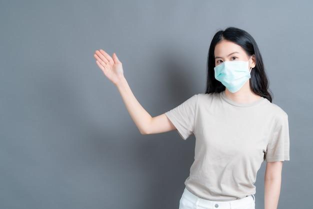 Jonge aziatische vrouw met medisch gezichtsmasker beschermt filterstof pm2.5 anti-vervuiling, anti-smog en covid-19 met handpresentatie aan de zijkant