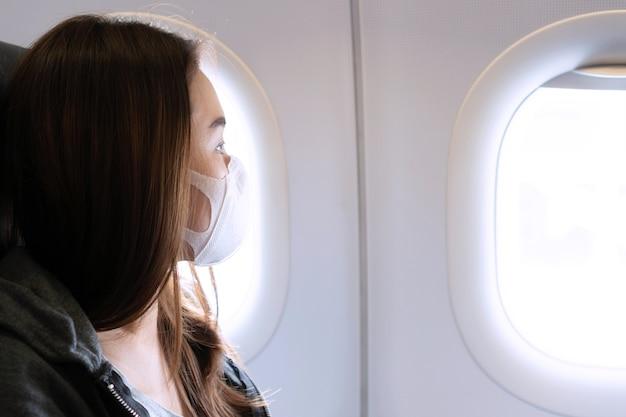 Jonge aziatische vrouw met medische gezichtsmaskerzitting op vliegtuig. bescherming coronavirus covid-19-concept.