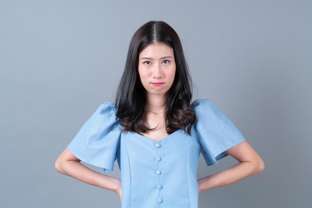Jonge aziatische vrouw met mokkend gezicht in blauwe kleding op grijs