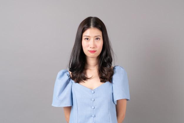 Jonge aziatische vrouw met mokkend gezicht in blauwe kleding op grijze muur