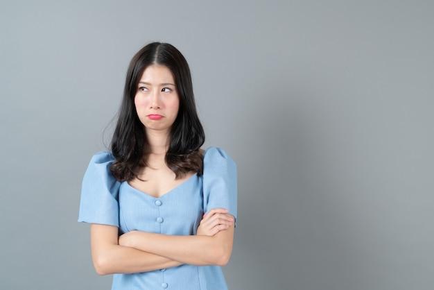 Jonge aziatische vrouw met mokkend gezicht in blauwe kleding