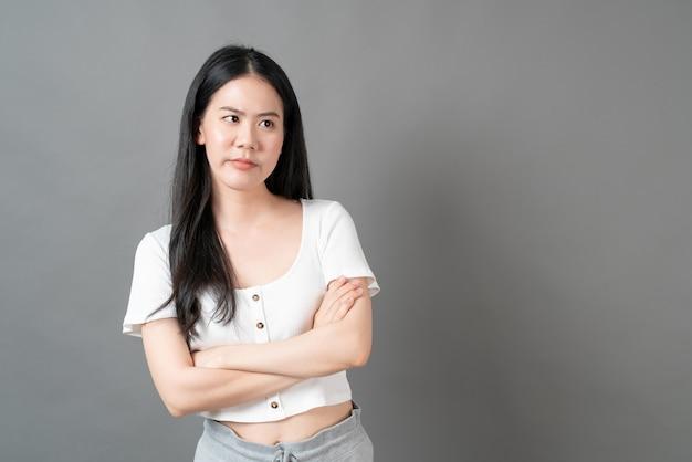 Jonge aziatische vrouw met mokkend gezicht in wit overhemd op grijze oppervlakte