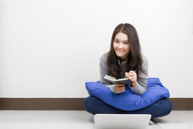 Jonge aziatische vrouw met notitieboekje en laptop in de kamer zitten. gelukkig smileygezicht.