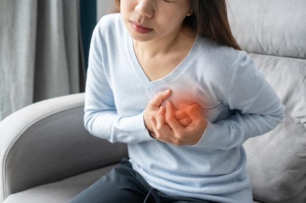 Jonge aziatische vrouw met pijn in het hartgebied. vrouw die lijdt aan hartpijn pijnlijke borst. gezondheidszorg, medisch concept.