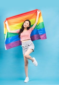 Jonge aziatische vrouw met regenboogvlag ter ondersteuning van lgbtq + -gemeenschap op blauw