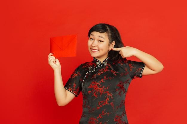 Jonge aziatische vrouw met rode envelop die op rode muur wordt geïsoleerd