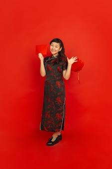 Jonge aziatische vrouw met rode envelop en chinese lantaarn die op rode muur wordt geïsoleerd