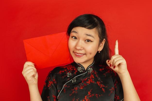 Jonge aziatische vrouw met rode envelop