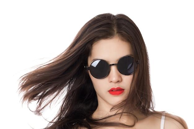 Jonge aziatische vrouw met rode lippen die zonnebril draagt en van haar haar schudt.