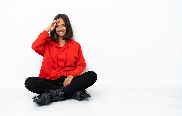Jonge aziatische vrouw met rolschaatsen op de vloer die met hand met gelukkige uitdrukking groeten