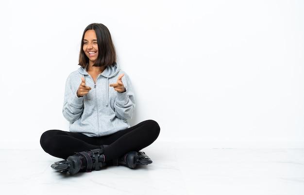 Jonge aziatische vrouw met rolschaatsen op de vloer die naar voren wijzen en glimlachen