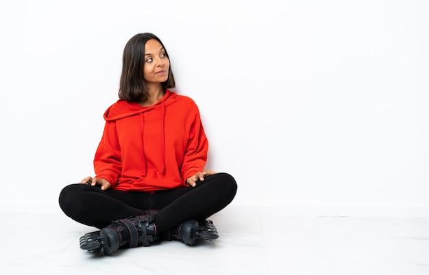 Jonge aziatische vrouw met rolschaatsen op de vloer die twijfels hebben terwijl op zoek kant
