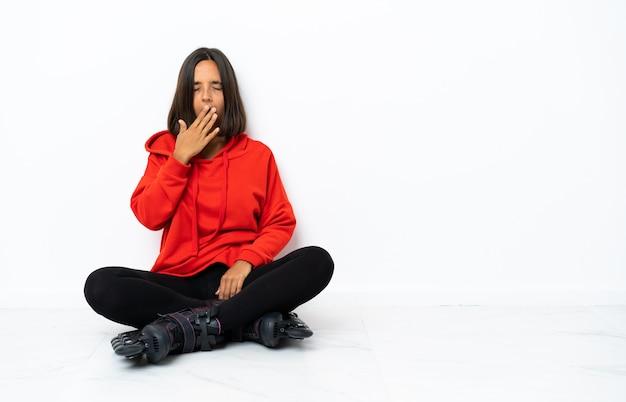 Jonge aziatische vrouw met rolschaatsen op de vloer geeuwen en kegel wijd open mond met hand