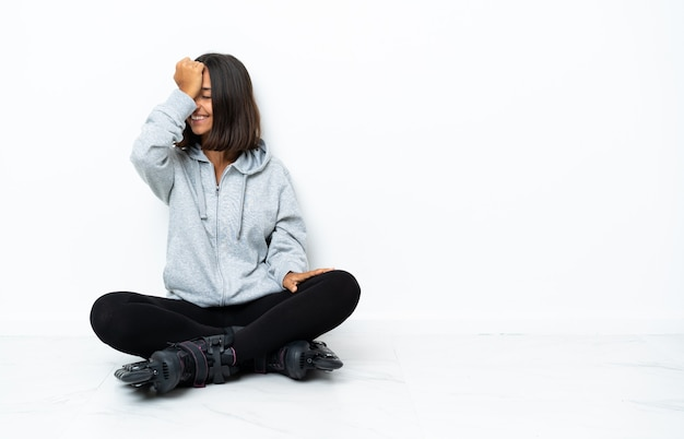 Jonge aziatische vrouw met rolschaatsen op de vloer heeft iets gerealiseerd en de oplossing voor ogen