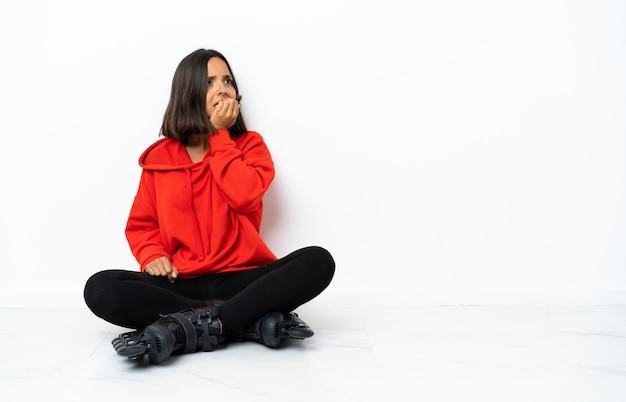 Jonge aziatische vrouw met rolschaatsen op de vloer is een beetje zenuwachtig