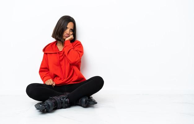 Jonge aziatische vrouw met rolschaatsen op de vloer met vermoeide en verveelde uitdrukking