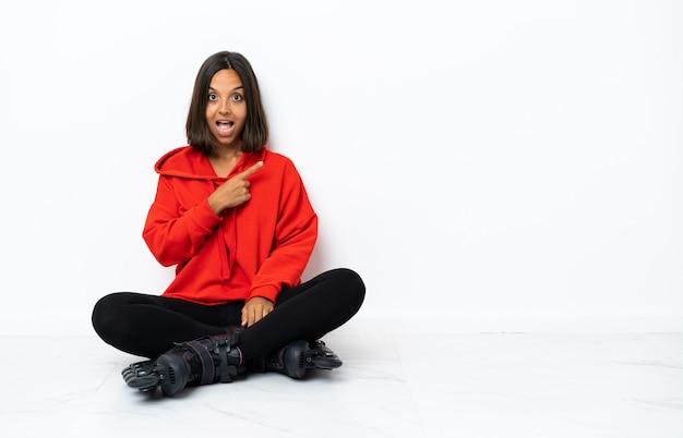 Jonge aziatische vrouw met rolschaatsen op de vloer verrast en wijzende kant