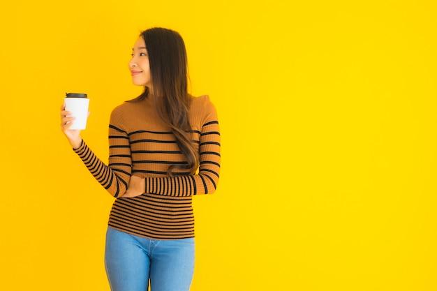 Jonge aziatische vrouw met rugzak en koffiekopje in haar hand op geel