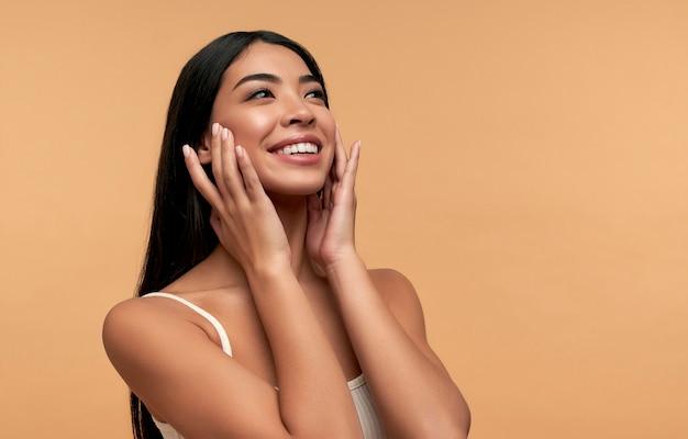 Jonge aziatische vrouw met schone gezonde gloeiende huid in witte bovenkant die op beige wordt geïsoleerd
