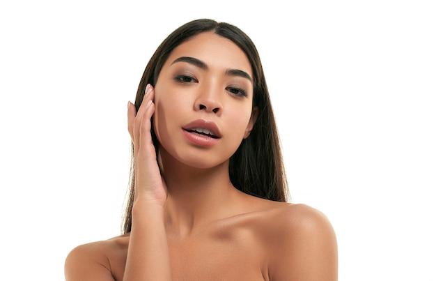 Jonge aziatische vrouw met schone stralende gezonde huid die op wit wordt geïsoleerd