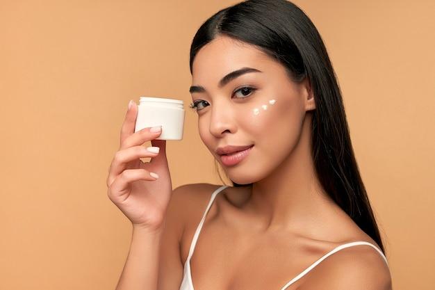 Jonge aziatische vrouw met schone stralende huid gebruikt een hydraterende gezichtscrème op beige