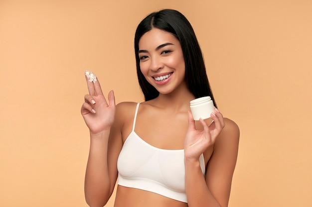 Jonge aziatische vrouw met schone stralende huid gebruikt een hydraterende gezichtscrème op een beige muur.