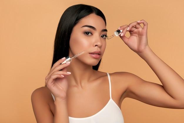 Jonge aziatische vrouw met schone stralende huid in witte lingerie gebruikt een hydraterend serum op een beige muur. Premium Foto