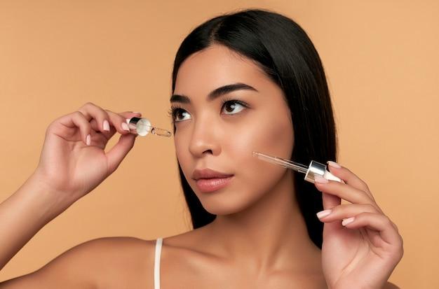 Jonge aziatische vrouw met schone stralende huid in witte lingerie gebruikt een hydraterend serum op een beige muur.