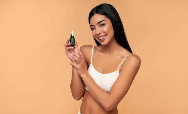 Jonge aziatische vrouw met schone stralende huid in witte lingerie houdt een hydraterend serum op beige