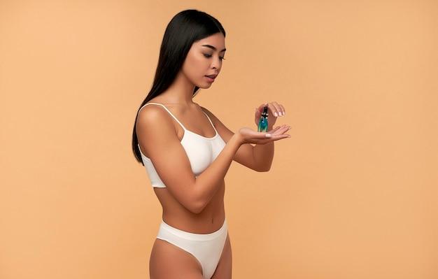 Jonge aziatische vrouw met schone stralende huid in witte lingerie houdt een hydraterend serum op een beige muur.