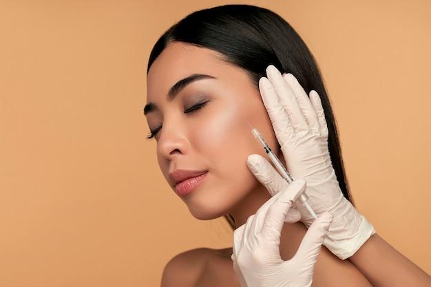 Jonge aziatische vrouw met schone stralende huid krijgt botox-injecties voor contourverstrakking, lipvergroting op beige