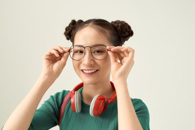 Jonge aziatische vrouw met smileygezicht dragen van een bril geïsoleerd op een witte achtergrond.