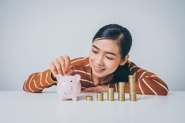 Jonge aziatische vrouw met stapel van munten en spaarvarken