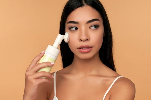 Jonge aziatische vrouw met stralende huid reinigt haar gezicht met een borstel en schuim geïsoleerd op beige