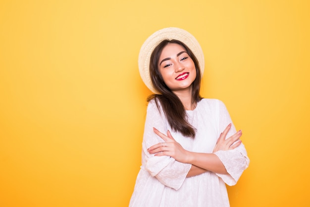 Jonge aziatische vrouw met strohoed die op gele muur wordt geïsoleerd