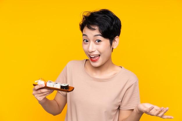 Jonge aziatische vrouw met sushi met geschokte gelaatsuitdrukking