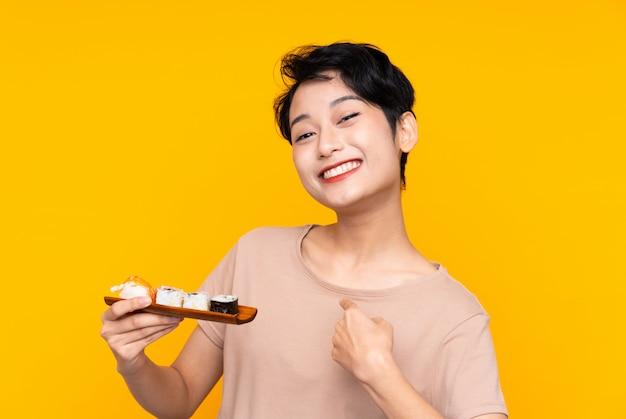 Jonge aziatische vrouw met sushi met verrassingsgelaatsuitdrukking